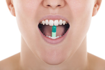 Open mouth with pill between teeth