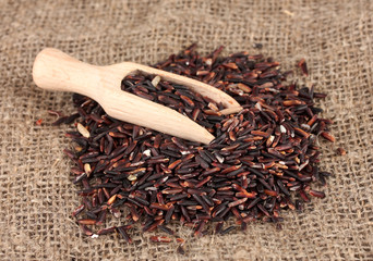 black rice  in wooden  scoop on bamboo mat