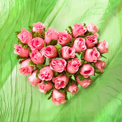 Pink rose heart on the green cloth drapery
