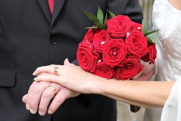 Newlywed couple hands and bouquet