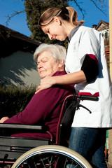 Altenpflegerin schiebt Seniorin im Rollstuhl durch einen Garten