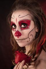 Портрет девушки с рисунком на лице и розой