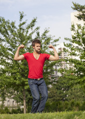 fun young man playing with his muscles outdoors