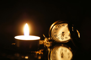 Vintage pocket watch, with burning candle