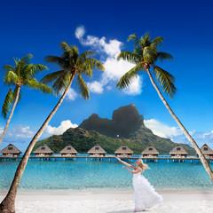 bride on a beach with palm and mountain. Bora-Bora. Polynesia
