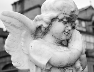 statue of little praying angel on cemetery