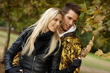 Loving couple walking in park at autumn