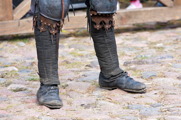 Legs of a man in the boots of a dark ages