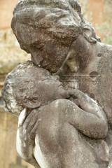 child in mother's arms - sculpture on italian cemetery