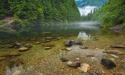 Fototapete - Clear Lake With Rocks and Mist in Distance