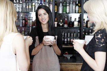 Women chatting over coffee at wine bar