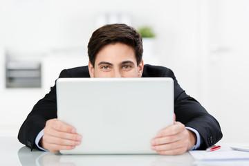 lächelnder mann im büro schaut über laptop