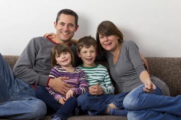 Familie sitzt auf dem Sofa