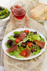 salad with prosciutto, tomato and olives on the plate