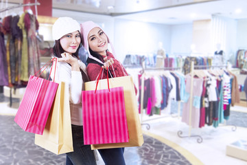 Shopaholic friends holding bags in the mall
