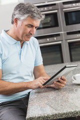 Man Using Tablet Computer in Kitchen Drinking Coffee