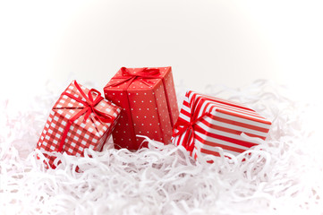 Gift boxes with xmas presents wrapped in red paper with ornament