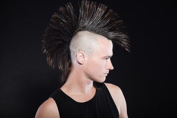 Punk man with mohawk haircut. Expressive face. Against black.