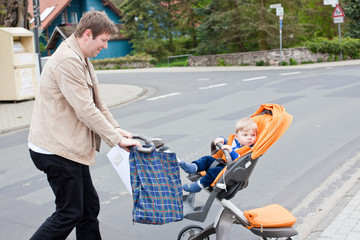 Young father walking with baby toddler in pram