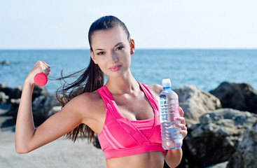 Girl doing sports with weights and holding a bottle of water
