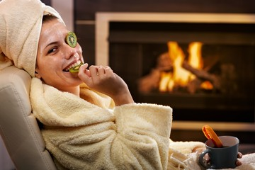 Funny woman eating fruit from facial mask