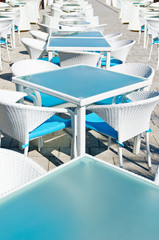 Rows of empty tables and chairs in an open air cafeteria