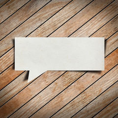 Paper speech bubble on wood background
