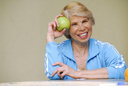 Señora feliz sujetando y comiendo una manzana verde.