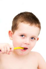 Little boy in the bath tub brushing his teeth