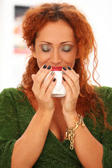 Beautiful and attractive redhead holding cup
