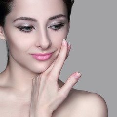 Beautiful woman with healthy skin touching hand face isolated on