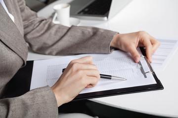 Hand mit Stift und Klemmbrett