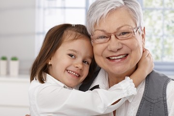Cute little girl hugging grandmother