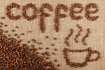 Coffee title with cup laid out from coffee beans on a burlap