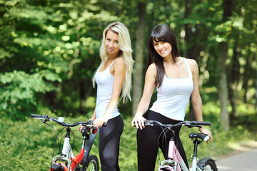 Portrait of pretty young women with bicycle in a park smiling -