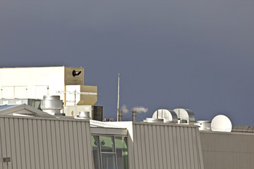 Equipment on rooftop of buildings and blue sky