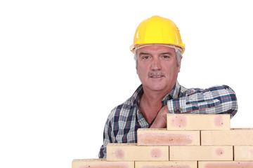 Artisan leaning on stack of bricks