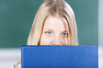 studentin schaut über aktenordner