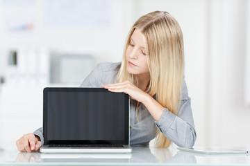 blonde frau zeigt etwas am laptop