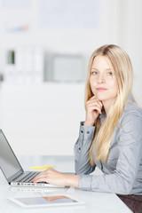 junge angestellte mit laptop im büro