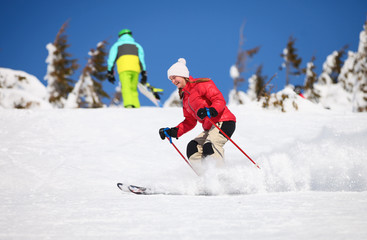Young female skier on a snowy slope
