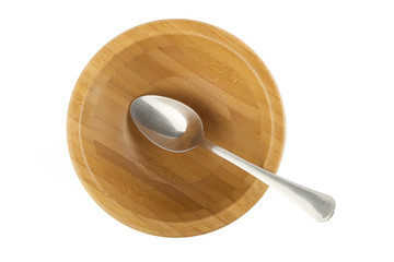 steel spoon in wood bowl isolated on white