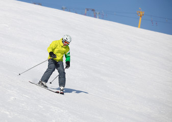 Young man learning to ski on a snowy slope