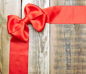 red bow and ribbon on the old wooden background