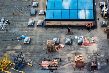 Construction site, roof with two workmen and building material