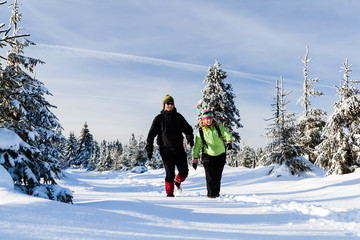 Couple hiking on snow in winter mountains