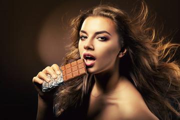 passionate woman biting chocolate bar