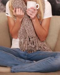 Frau sitzt mit Tasse Kaffee auf dem Sofa