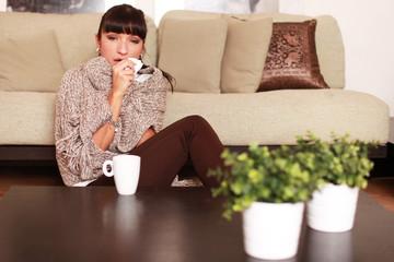 kranke Frau sitzt im Wohnzimmer