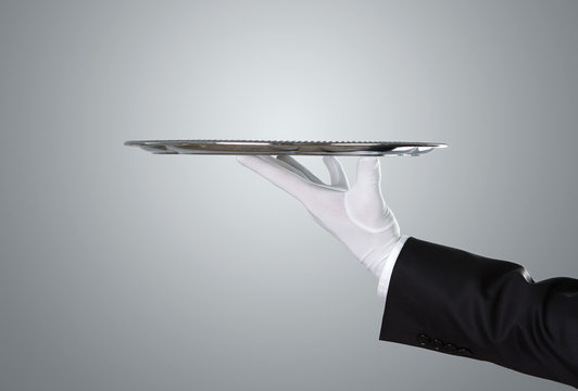 Waiter holding empty silver tray over gray background with copy